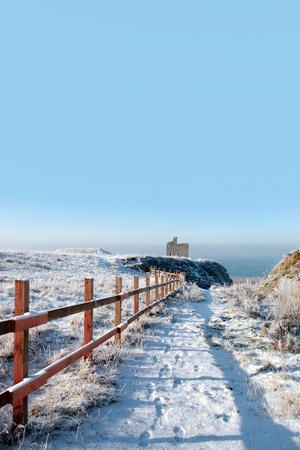 ballybunion: snow covered view of atlantic ocean and castle in ballybunion on a frosty snow covered winters day