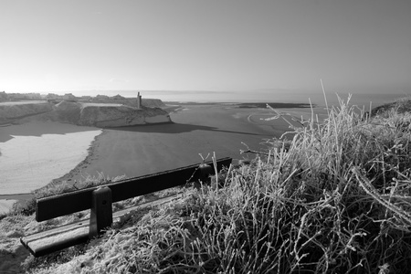 bleak: beach and ballybunion castle with a bench on a frosty snow covered winters day in black and white