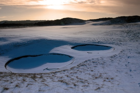 rakes in bunkers on a snow covered links golf course in ireland at sundown in snowy winter weather