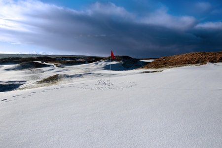 red flag on a snow covered links golf course in ireland in stormy winter weather photo