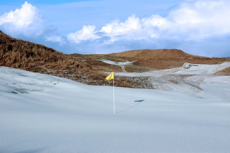 yellow flag on a snow covered links golf course in ireland in winter photo