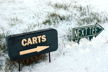 carts and next tee sign on a snow covered links golf course in ireland in snowy winter weather photo