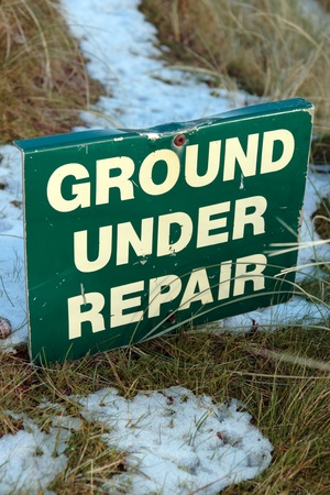 ground under repair sign on a snow covered links golf course in ireland in snowy winter weather photo