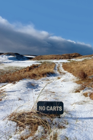 no carts sign on a snow covered links golf course in ireland in snowy winter weather photo