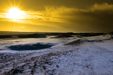 bunkers on a snow covered links golf course in ireland at sundown in snowy winter weather