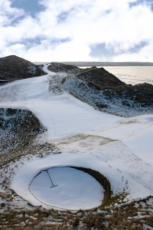 a rake in a bunker on a snow covered links golf course in ireland in snowy winter weather photo