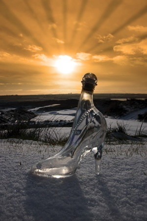 irish: a crystal glass slipper in a snow covered irish golf course at sunset for a concept on ladies golf