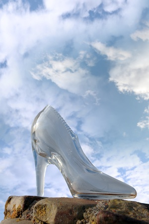 a glass slipper on a stone surface with a cloudy blue sky background photo