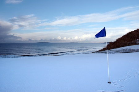 a snow covered links golf hole in ireland in winter weather with blue flag