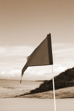 a snow covered links golf hole in ireland in winter weather with flag in sepia photo