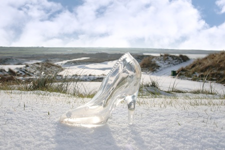 a crystal glass slipper in a snow covered irish golf course for a concept on ladies golf photo