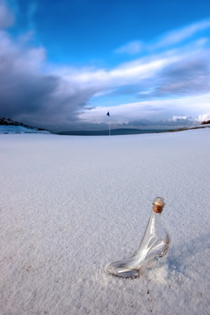 a glass slipper in a snow covered irish golf course for a concept on ladies golf photo