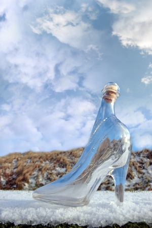 a glass slipper on a snow covered surface with a cloudy sky background photo