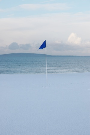 a snow covered links golf hole in ireland in winter weather with blue flag photo