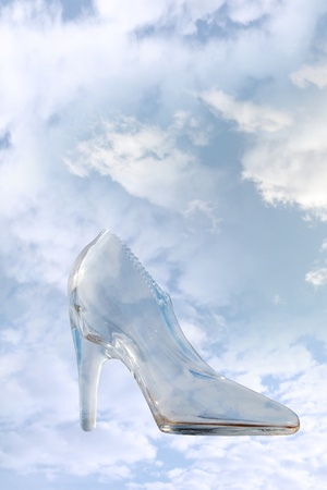 a glass slipper in a cloudy blue sky background with clipping path photo