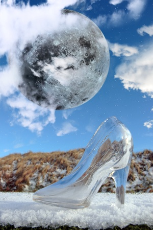a glass slipper in a cloudy blue sky background with full moon at midnight photo
