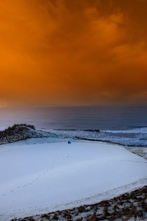 a snow covered links golf hole in ireland with blue flag and orange sunset sky