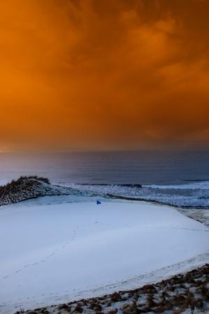 una cubierta de nieve agujero campo de golf en Irlanda con la bandera azul y naranja puesta de sol cielo Foto de archivo