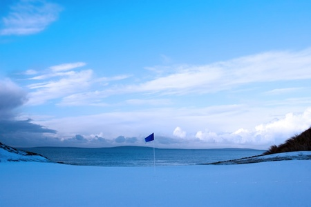 a snow covered links golf hole in ireland in winter evening weather with blue flag photo