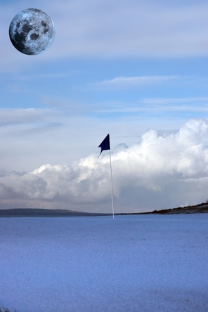 a snow covered links golf hole in ireland with blue flag and full moon in sky photo