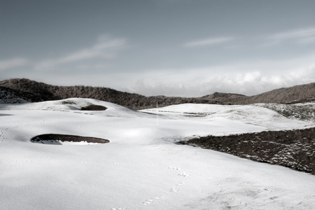 bunkers on a snow covered links golf course in ireland on a grey day in snowy winter weather photo