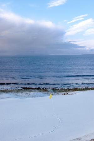 a snow covered links golf hole in ireland in winter weather with yellow flag photo