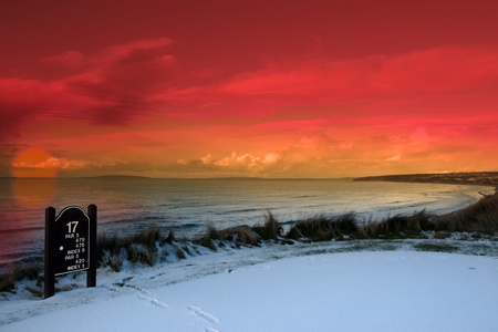 a snow covered links golf hole in ireland with seventeen tee sign and orange sunset sky photo
