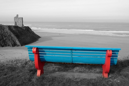 ballybunion bench in winter with view of beach castle and cliffs in black and white except bench photo
