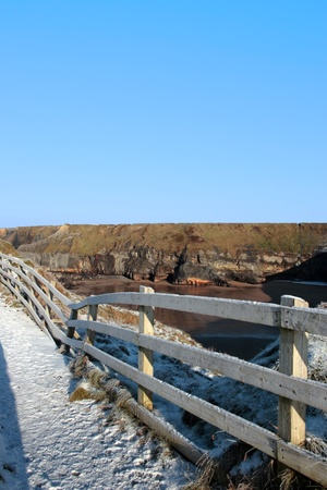 frosty blue winters view at ballybunion cliffside walk with bright sunshine and fence photo