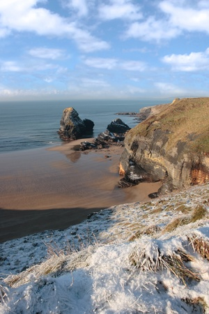 yule tide: snow covered view of beach cliffs and the virgin rock in ballybunion county kerry ireland