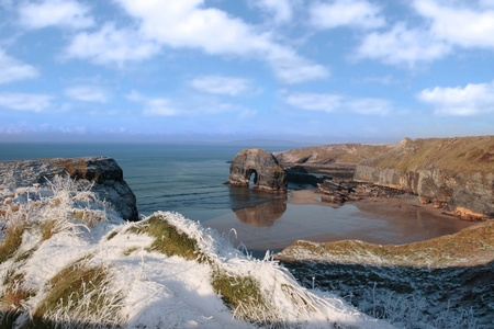 snow covered view of beach cliffs and the virgin rock in ballybunion county kerry ireland photo