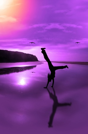 a happy young woman celebrating on an isolated irish beach in motion Stock Photo - 12008083