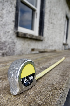 builders diy tape measure on scaffolding with building site in the background photo