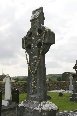 celtic cross in a christian church graveyard decorated with wooden rosary beads photo