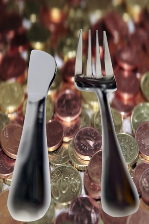 penny pinching: fork and knife isolated against a money background with a clipping path as in eating out cheaply Stock Photo