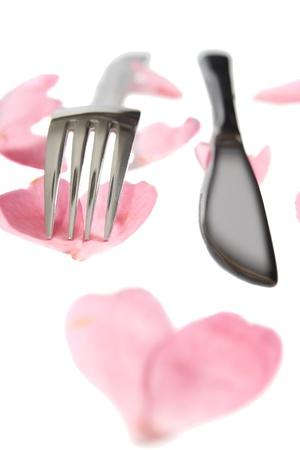 fork and knife isolated with rose petals for concept on romantic dining photo