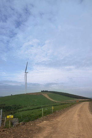 county tipperary: dirt road to a windmill on lush irish countryside landscape in glenough county tipperary ireland