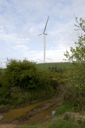 county tipperary: wet mucky dirt road to a windmill on lush irish countryside landscape in glenough county tipperary ireland Stock Photo
