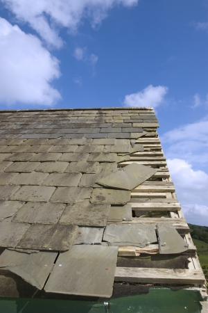damaged roof: broken and fallen slate leaves holes in a roof due to storm or decay Stock Photo