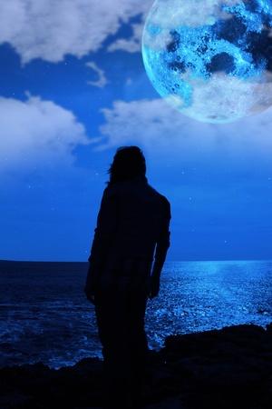 sadly: una donna sola guardando tristemente sul bordo della scogliera sotto la luna piena, come se il peso del mondo sulle spalle Archivio Fotografico