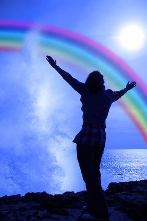 gratitudine: sagoma di una donna sola alzando le braccia in soggezione e lode presso la potenza della natura