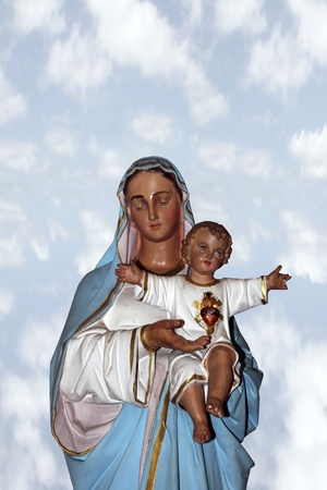 statue of the virgin mary holding jesus christ as a baby with a clipping path photo