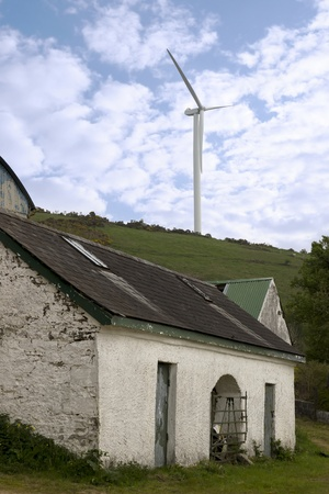 county tipperary: windmill above abandoned farm on lush irish countryside landscape in glenough county tipperary ireland
