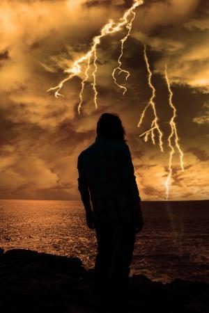 mujer mirando el horizonte: una mujer sola mirando con tristeza el borde de los acantilados en el condado de Clare Irlanda durante una tormenta