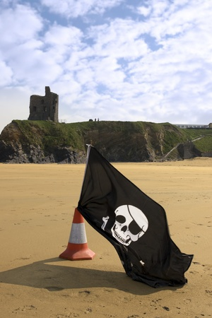 sandy golden beach with jolly roger flag in ballybunion county Kerry Ireland with castle in background photo