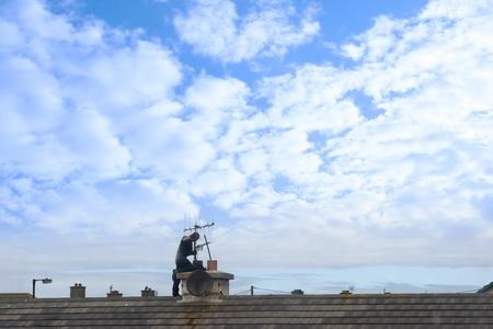 schoorsteenveger aan het werk op het dak van een woonwijk