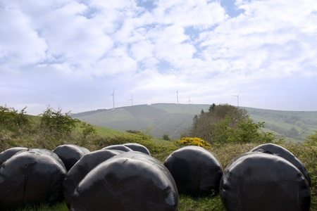 county tipperary: windmill on lush irish countryside landscape in glenough county tipperary ireland with plastic wrapped bales in foreground