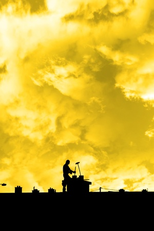 silhouette of a chimney sweep at work on the rooftop of a housing estate with sunset sky in background Stock Photo