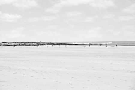 sandy beach with children getting ready to be taught surfing in ballybunion county Kerry Ireland in black and white photo