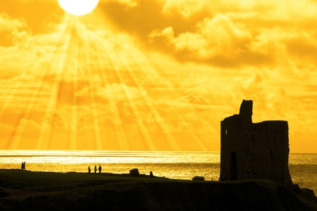 old castle in Ballybunion county Kerry Ireland at sunset with tourists and sun rays in background photo